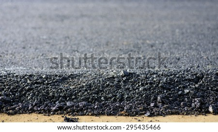 layer of asphalt raw material in a shallow dept of field - stock photo