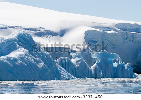 layer of blue icebergs in front of snow
