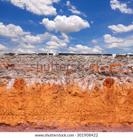Layer of soil beneath the asphalt road with blue sky - stock photo