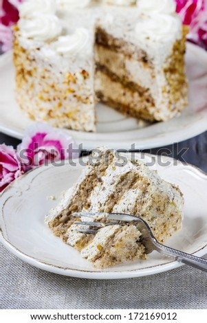 Layer vanilla and chocolate cake. Bouquet of pink carnations in the background - stock photo
