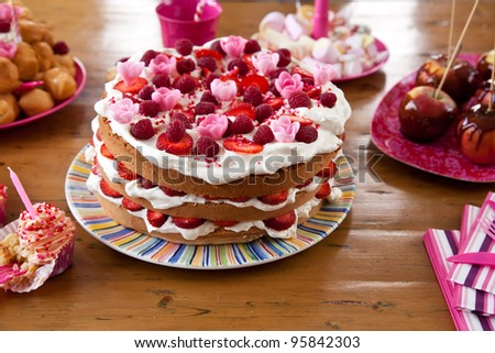 Layered birthday cake amid other snacks on a table