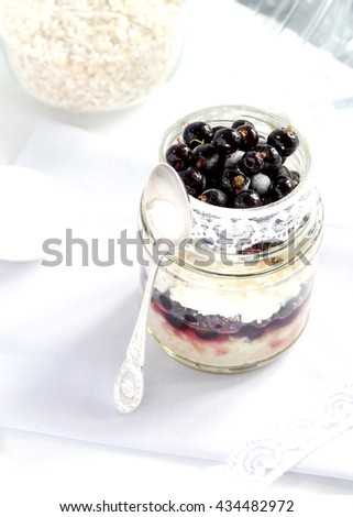 Layered dessert with blackcurrant, cottage cheese and oat flakes in a glass jar. Selective focus - stock photo