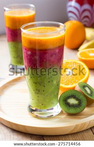 Layered fruit smoothie made of kiwi, banana, sweet cherry, orange and sea buckthorn - stock photo