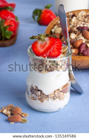 Layered granola and yogurt dessert in a glass with strawberries and granola on background