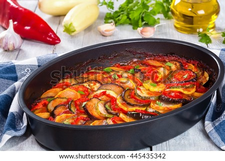 Layered ratatouille in a baking dish, slices of zucchini, red bell pepper, chili, yellow squash, eggplant, olive oil, parsley and garlic on a white background, close-up