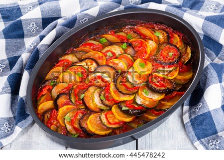 Layered ratatouille in a baking dish, slices of zucchini, red bell pepper, chili, yellow squash, eggplant, olive oil, parsley and garlic on a white background, close-up - stock photo