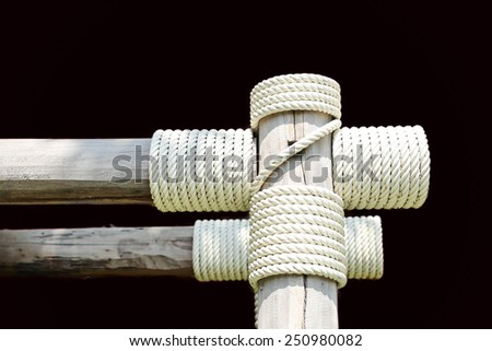 Layers of rope tied around a wooden log in black background - stock photo