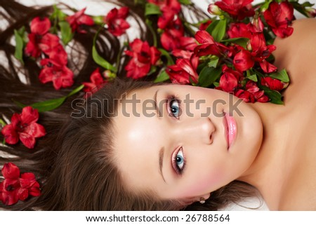 Laying beautiful  young woman with flowers in hair