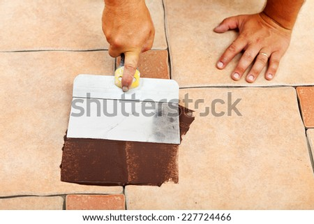Laying ceramic floor tiles - hands apply the joint material with specific tool - stock photo