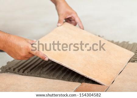 Laying ceramic floor tiles - man hands fitting the next piece, closeup - stock photo