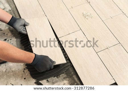 Laying Ceramic Tiles. Man placing ceramic floor tile in position over adhesive - stock photo