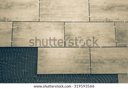 Laying ceramic tiles on a special cement grout. Selective focus. Shallow depth of field. Toned. - stock photo