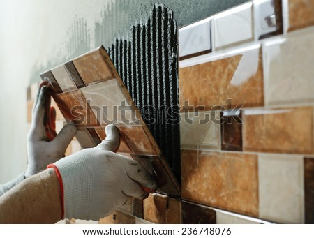 Laying Ceramic Tiles. Tiler placing ceramic wall tile in position over adhesive - stock photo