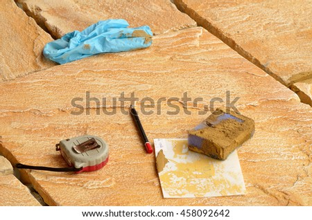 Laying concrete outdoor tiles, sandstone colored paving on the terrace , meter, rubber gloves and sponge with grout - stock photo