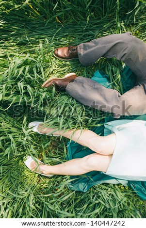 Laying couple in the high grass, top perspective, only legs, engagement photo, before wedding, picnic, sunny day, romantic photo, without face, girl with turquoise dress, vintage color - stock photo