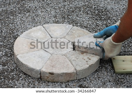 Laying decorative pavers in a circular pattern - stock photo