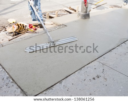 Laying down new sidewalk in urban setting - stock photo