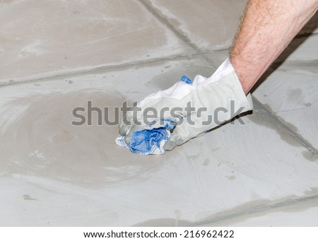 Laying floor tiles, tiler cleaning tiles after filling up joints - stock photo