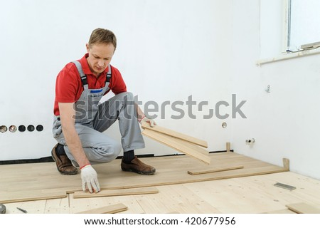 Laying hardwood parquet. Worker fixes the boards one by one.