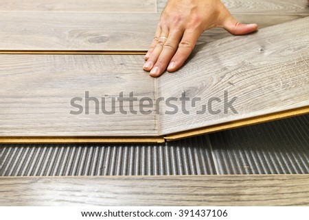 Laying laminate flooring in a flat the hands of master closeup - stock photo