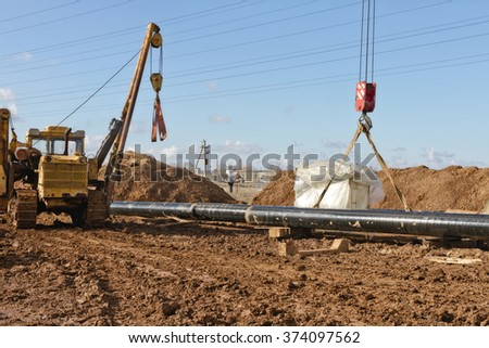 laying of gas main in a trench dug in the field near the power line. - stock photo