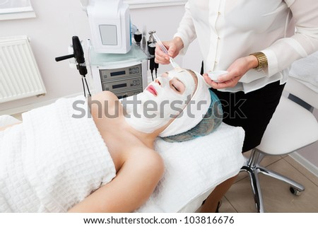 laying of mudpack in modern beauty salon - stock photo