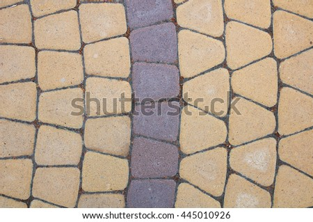 Laying of paving slabs triangular. Two colors of yellow and brown. Example stacking. Photo vertically downwards. As texture or background. Radial recurrent line.