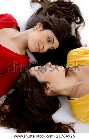 laying sisters looking to each other against white background - stock photo