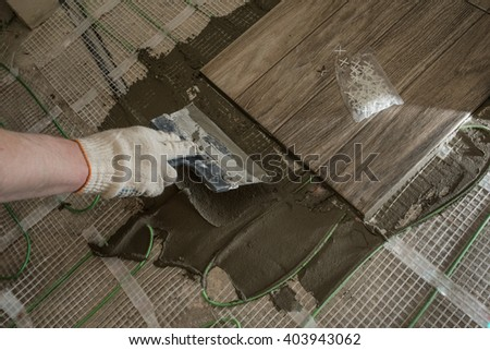 Laying tile glazed tile stylized tree. Prepared under the concrete floor insulation. - stock photo