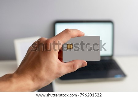 Layout credit card in hand with a laptop in the background