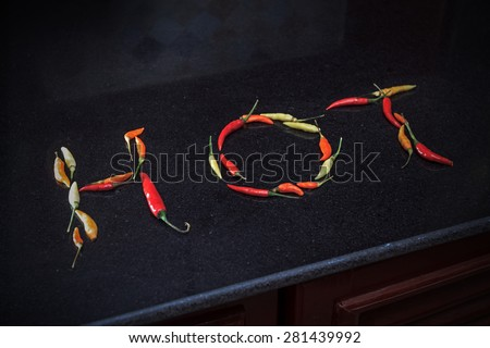 Layout of multicolor chili peppers forming a word on black marble background view 2 - stock photo