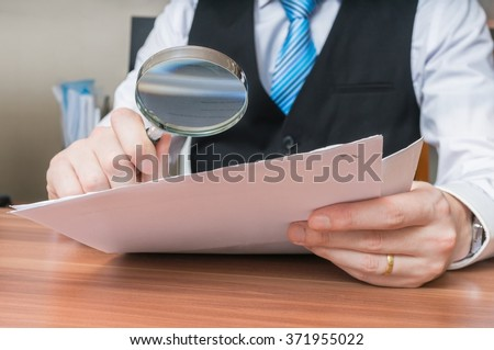 Laywer is analysing document with magnifying glass. - stock photo