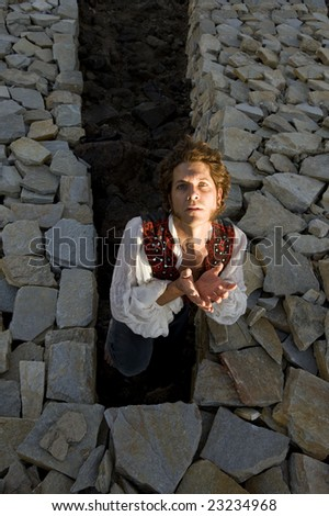 Lazarus. Man raising up from a stone structure. - stock photo