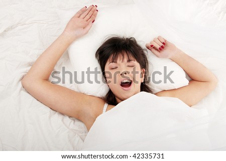 Lazy beautiful woman in bed stretching and yawns - stock photo