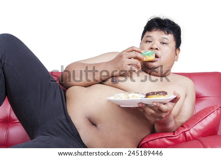 Lazy fat person eating donuts while sitting on the sofa, isolated on white background - stock photo
