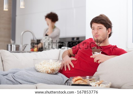 Lazy guy and his hard-working wife in the kitchen - stock photo