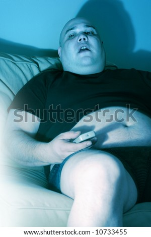 Lazy overweight male sitting on a couch watching television.  Harsh blue lighting from television with slow shutter speed to create TV watching atmosphere. - stock photo