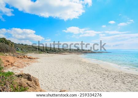 Le Bombarde beach under a cloudy sky in springtime. Shot in Alghero, Italy - stock photo