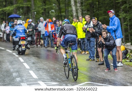 LE MARKSTEIN, FRANCE - JUL 13: Michael Albasini of Orica-GreenEDGE team climbing the road to mountain pass Le Markstein in Vosges Mountains during the stage 9 of Le Tour de France on July 13, 2014. - stock photo