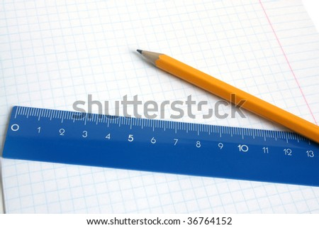 Lead pencil and blue ruler on a school writing-book