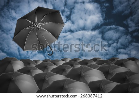 Leader concept, one umbrella fly out from the group of black umbrellas - stock photo
