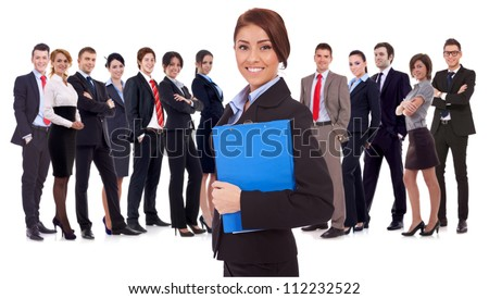 Leader holding a clipboard with business team behind, isolated on white. successful happy businessteam with a young woman as a leader, holding a notepad and looking at the camera