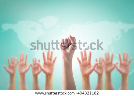 Leader's fist victory sign among blur hands crowd group: Many people blurred palms raising up upward on vintage blue sky background map: World participation, leadership, volunteer concept  - stock photo