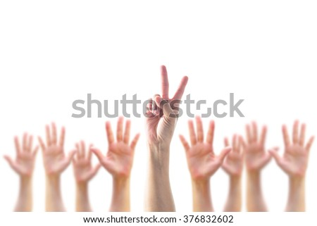 Leader's two fingers victory sign among blur hands crowd group:: Many people blurred palms raising up upward isolated on white sky background: World participation, leadership, volunteer concept - stock photo