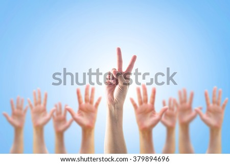 Leader's two fingers victory sign among blur hands crowd group: Many women people blurred palms raising up upward on blue sky background: World participation, leadership, volunteer concept: V day  - stock photo