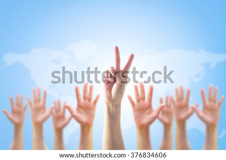Leader's two fingers victory sign among blur person's hands crowd group: Many people blurred palms raising up upward on blue sky background map: World participation, leadership, volunteer concept - stock photo