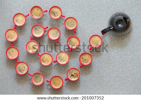 Leaders are the givers, decorative helical or spiral pattern of freshly poured frothy black coffee in red mugs with a full coffee pot at the end as though leading the line, view form above - stock photo