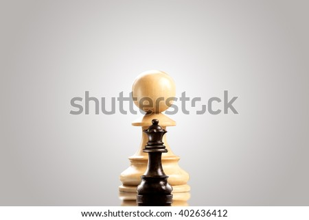 Leadership and bravery concept; huge white wooden pawn staying against a small black queen. - stock photo