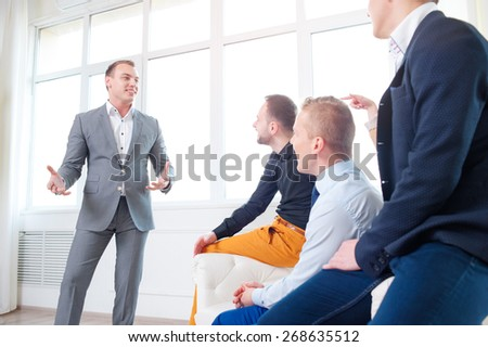 Leadership and charisma. Business speech. Handsome young man in grey suit talking to his colleagues - group of young people. - stock photo