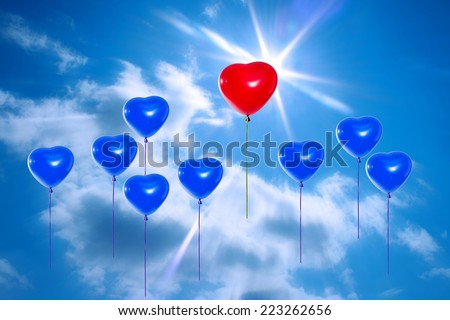 Leadership concept. Group of balloons rise up into the sky, one of them red. - stock photo
